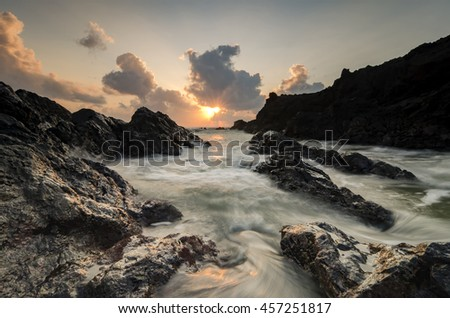 waves splashing on the unique rocks formation over stunning sunrise background.Sunlight covered with dark clouds.soft focus image due to long exposure