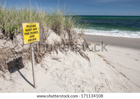 Waves wash up against a dune on a Cape Cod beach during a sunny morning. Waves and wind, in association with sea level rise, are eroding many coastlines throughout the east coast and the world. - stock photo