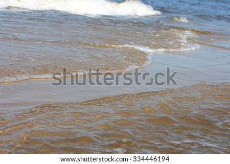 Waves with whitecaps flood the sandy beach