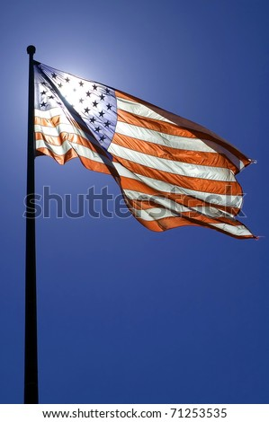 waving american flag, clear blue sky, sun is directly behind the flag - stock photo