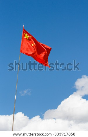 Waving Chinese flag against blue sky above white clouds - stock photo
