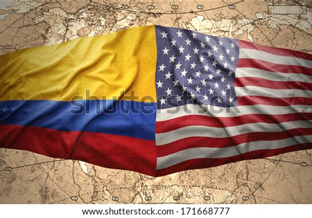 Waving Colombian and American flags on the of the political map of the world