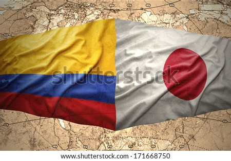 Waving Colombian and Japanese flags on the of the political map of the world - stock photo