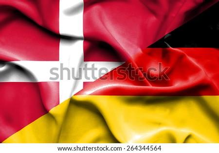 Waving flag of Germany and Denmark - stock photo