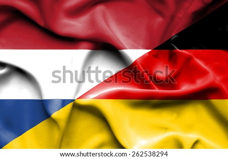 Waving flag of Germany and Netherlands - stock photo