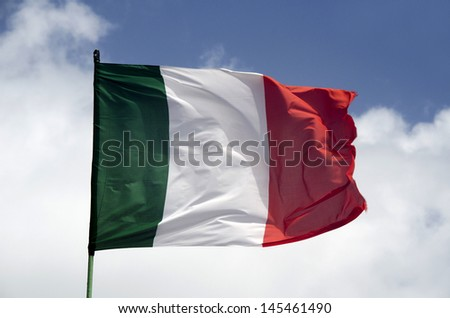 waving flag of Italy against blue sky and clouds