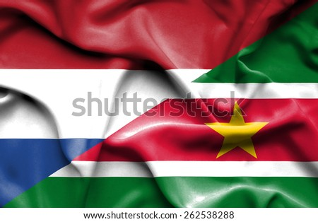 Waving flag of Suriname and Netherlands - stock photo