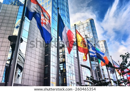 Waving flags in front of European Parliament building. Brussels, Belgium - stock photo