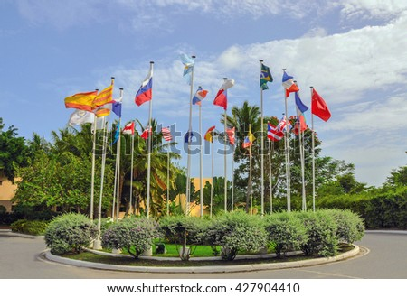 Waving flags representing different countries with blue sky background - stock photo