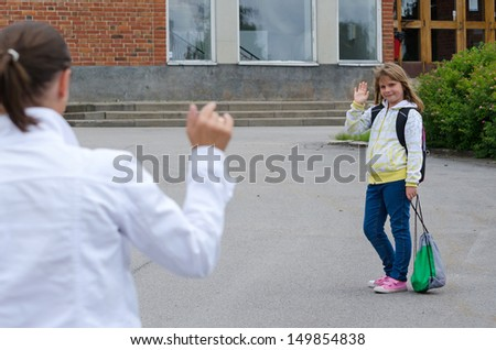 Waving goodbye before the school - stock photo