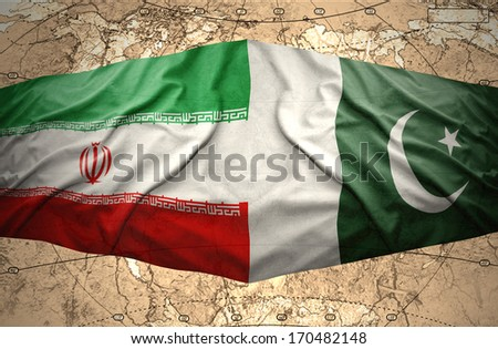 Waving Pakistani and Iranian flags on the of the political map of the world - stock photo