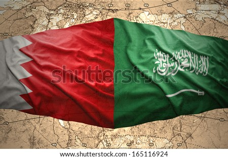 Waving Saudi Arabia and Bahraini flags on the background of the political map of the world