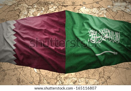 Waving Saudi Arabia and Qatar flags on the background of the political map of the world