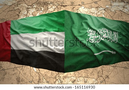 Waving Saudi Arabia and United Arab Emirates flags on the background of the political map of the world - stock photo
