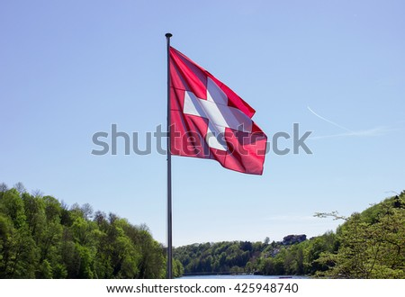 waving swiss flag over river and forest - stock photo