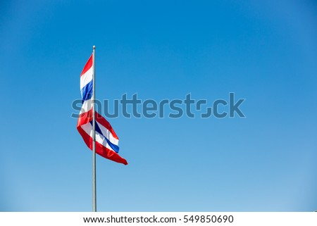 waving Thai flag of Thailand with blue sky background.