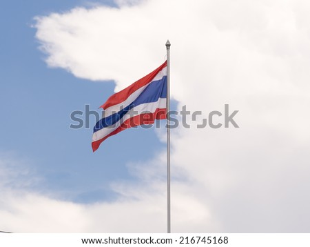 Waving Thai national flag with clouds and blue sky background. - stock photo