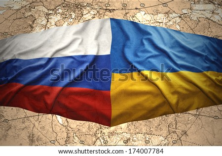 Waving Ukrainian and Russian flags of the political map of the world - stock photo