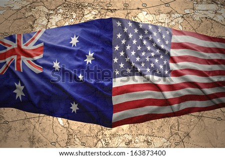 Waving United States of America and Australian flags on the background of the political map of the world - stock photo