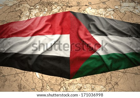 Waving Yemeni and Palestinian flags on the of the political map of the world - stock photo