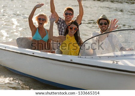 Waving young people in sunglasses sitting in motorboat summertime - stock photo