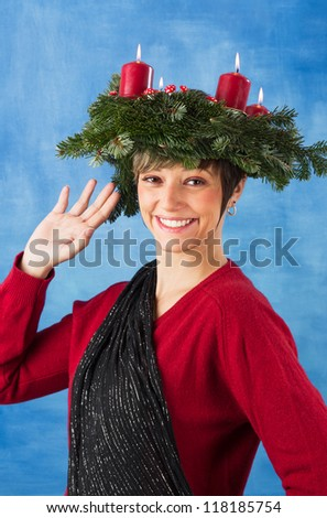 Waving young woman woman wearing advent wreath on her head, four candles are burning. Studio shot against a blue background, series - stock photo