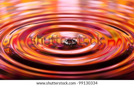 Wavy circles on the water, red and orange reflections.