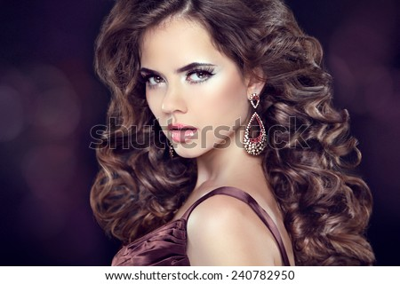 Wavy hair. Attractive girl with makeup. Jewelry Earring. Expressive eyes stare. Elegant lady over studio dark background. Luxury style.