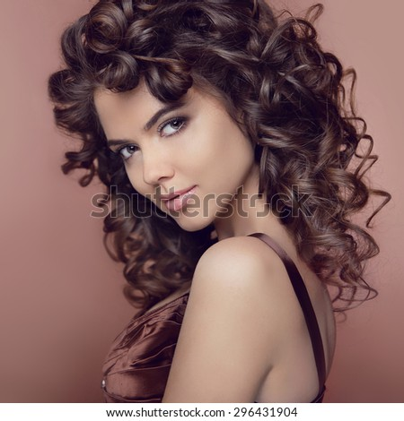 Wavy hair. Attractive smiling girl with makeup. Curly hairstyle. Brunette. Expressive eyes stare. Elegant lady over studio beige background. Luxury vogue style