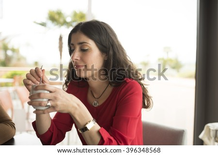 Wavy haired brunette sitting in cafe while holding cup of coffee