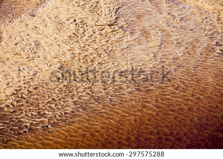 Wavy sand texture patterns on the bottom of the river in red - stock photo