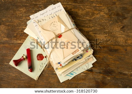 Wax seal next to a bundle of old letters on an antique wooden table - stock photo
