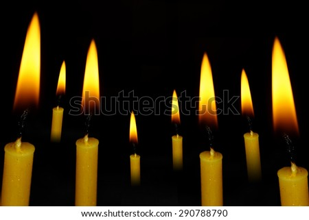 Wax yellow candle on abstract dark background. - stock photo
