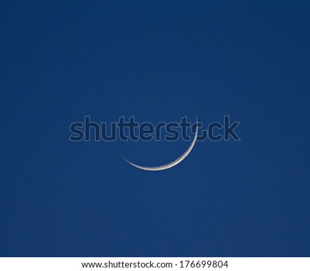 Waxing Crescent Moon during late afternoon against blue sky - stock photo