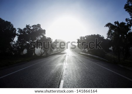 way road in front of the sun - stock photo