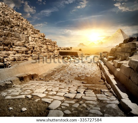Way through ruins of egyptian pyramids and sun - stock photo