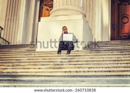 Way to Success. A black business man sitting on stairs of vintage style office building door way, working on laptop computer and talking on his mobile phone in the same time. Instagram filtered look.