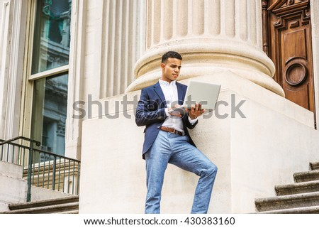 Way to Success. African American college student studying in New York, wearing blue blazer, white shirt, gray pants, standing against column outside office building, working on laptop computer.  - stock photo