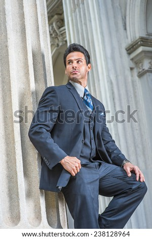 Way to Success. Dressing in dark blue three piece suit, necktie, a handsome, sexy, middle age businessman is standing against column outside office, confidently looking forward. Man Formal Fashion - stock photo