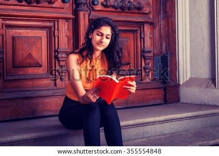 Way to Success. Power of Reading. East Indian American college student studying in New York, sitting on steps in front of vintage style library door way, looking down, reading red book, thinking.  - stock photo