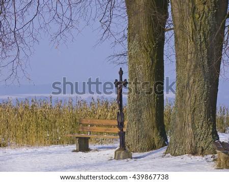 wayside cross beneath two big oaks in winter condition - stock photo
