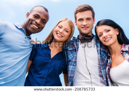 We are all good friends. Low angle view of four happy young people bonding and looking at camera with smile with blue sky in the background