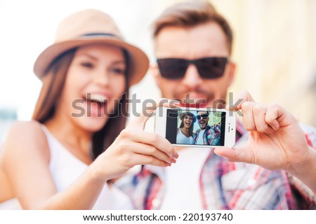 We are beautiful! Happy young loving couple making selfie while standing outdoors together  - stock photo