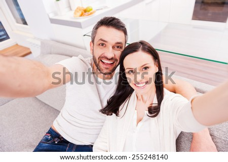 We are beautiful! Top view of happy loving couple bonding to each other and making selfie while sitting on the couch together - stock photo
