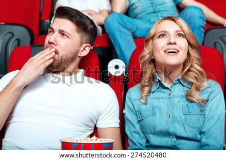 We are different. Young beautiful blond woman very interested in watching film and her neighbor really feels bored. - stock photo
