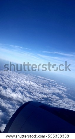 We are flying between white cloudy and blue sky