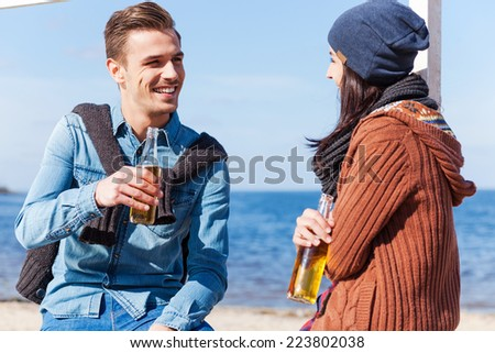 We are good friends. Handsome young man and woman talking to each other and smiling while drinking beer on the beach  - stock photo