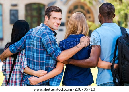 We are good friends. Rear view of handsome young man looking over shoulder and smiling while walking together with friends