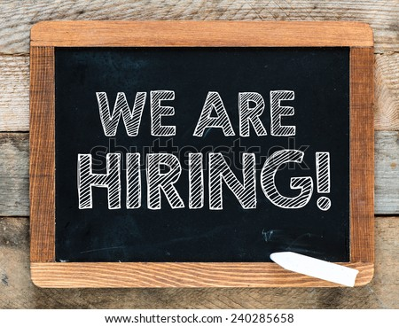 We are hiring background. We are hiring handwritten with white chalk on a blackboard - stock photo
