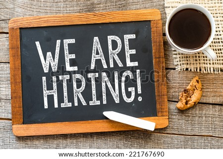 We are Hiring ! handwritten with white chalk on a blackboard, cup of coffee and biscuit on a wooden background  - stock photo